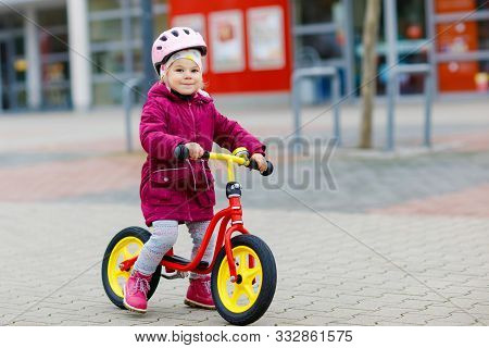 Cute Little Toddler Girl In Safety Helmet Riding On Run Balance Bike. Happy Healthy Lovely Baby Chil