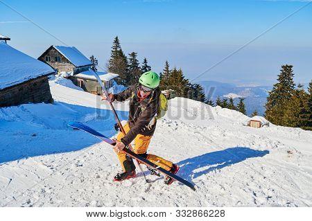 Clumsy Funny Skier Dropping His Wide Skis. Location: Poiana Brasov Ski Resort, Romania.