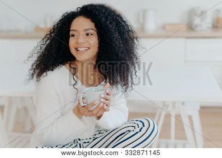 Photo Of Cute Cheerful Woman With Bushy Curly Hair Looks Away With Smile, Holds Mug Of Coffee, Wears