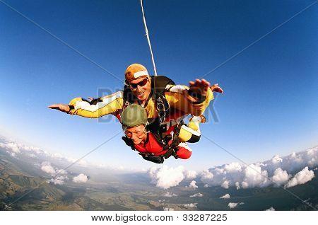 Tandem fallskärmshoppare leende i luften position över molnlandskap och jorden.