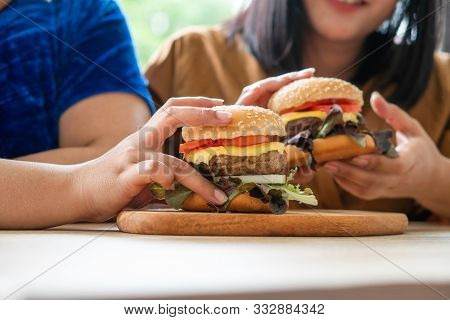 Hungry Overweight Woman Smiling And Holding Hamburger And Sitting In The Living Room, Her Very Happy