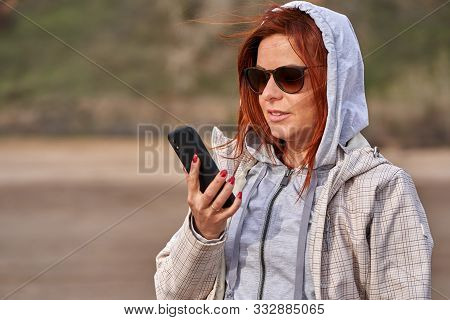 Portrait Of A Laughing Middle-aged Woman With Red Hair In Sunglasses With A Smartphone In His Hand F