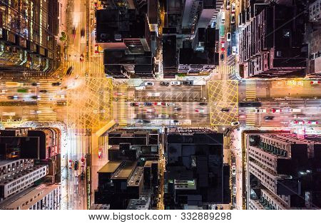 Car, Taxi, And Bus Traffic On Road Intersection At Night In Hong Kong Downtown District, Drone Aeria