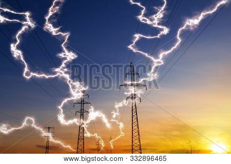 Power Line Against The Setting Sun With Flashes Of Electricity Discharges On Wires. Concept Of Curre