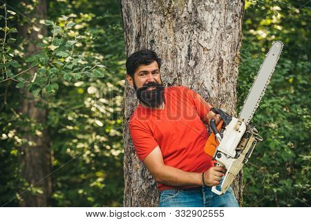 Lumberjack With Chainsaw On Forest Background. Lumberjack Holding The Chainsaw. Lumberjack In The Wo