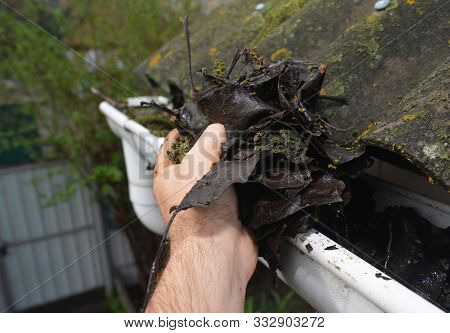 Roofer Cleaning House Rain Gutter From Leaves And Dirt In Autumn With Hands. Roof Gutter Cleaning Gu