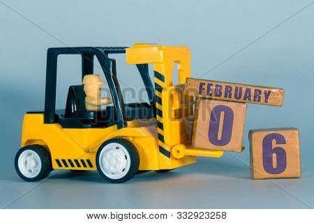 February 6th. Day 6 Of Month, Construction Or Warehouse Calendar. Yellow Toy Forklift Load Wood Cube