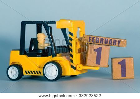 February 11th. Day 11 Of Month, Construction Or Warehouse Calendar. Yellow Toy Forklift Load Wood Cu