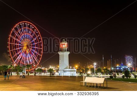 Seafront Promenade In Batumi At Night. Evening Illumination Lights In Ferris Wheel And Old Lighthous