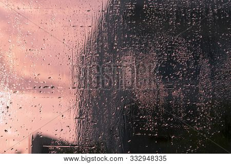 Wet Glittering Window Glass With Lots Of Transparent Rain Drops And A View Of The Pale Pink Sky And