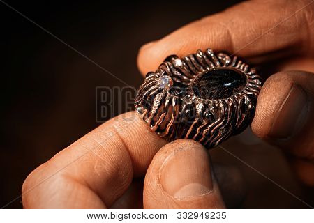 A Jeweler Is Holding An Unfinished Gold Ring With Precious Stones.