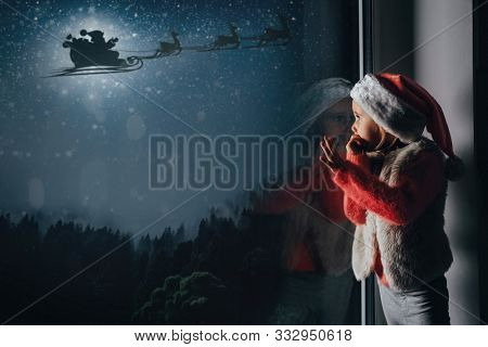 The child looks out the window on silhouette of a flying goth Santa Claus against the background of the night sky.