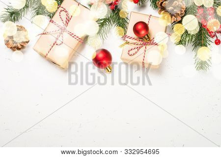 Christmas Background With Fir Tree And Decorations On White With Light Bokeh. Top View With Copy Spa