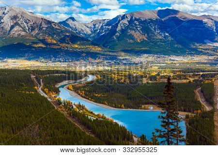 Lush multicolor autumn in the Canadian Rockies. The azure icy water of the Kananaskis River and Lake in the mountain valley of park. The concept of active, ecological and photo tourism
