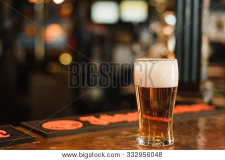 A Glass Of Beer In A Popular Bar. Pint Of Foamy Drink In A Restaurant. Mug With Beer At The Bar Coun