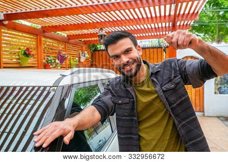 portrait of a young guy with keys near a car