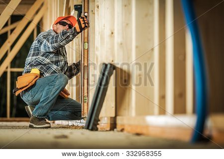 Caucasian Contractor Worker With Spirit Level Making Sure Wooden House Frame Is Leveled Correctly.