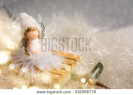 Toy Angel On Small Sledges With Festive Christmas Background