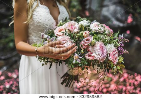 Woman Holding In Hands Big Wedding Bouquet In Rustic Style. Greens, Pink And White Roses, Coral Chry