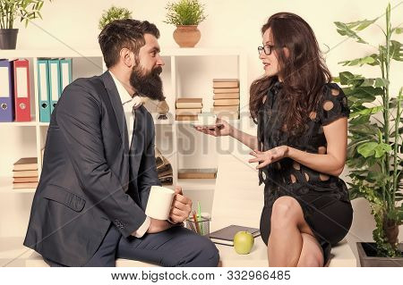 Discussion Over A Cup Of Tea. Professional Couple Participating In Business Discussion During Workin
