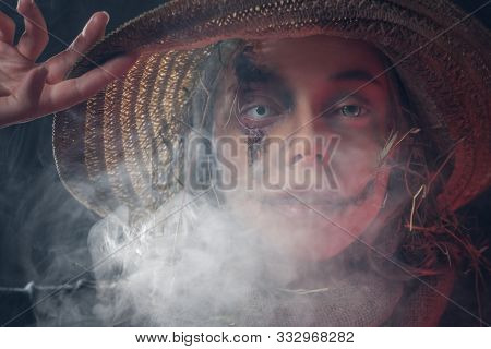 Beautiful Woman In Straw Hat And With Creepy Eye Lens Is Posing For Photographer In Smoke.
