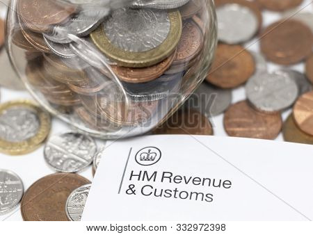 London / Uk - November 11th 2019 - Hmrc Logo Letterhead And Money Jar With Coins. Her Majestys Reven