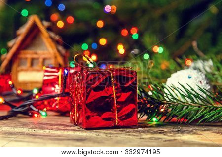 Christmas Composition. Christmas Balls, Red Small Gifts, Christmas Tree Branches On Toy House Backgr