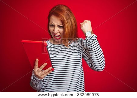 Young beautiful redhead woman using tablet over red isolated background annoyed and frustrated shouting with anger, crazy and yelling with raised hand, anger concept