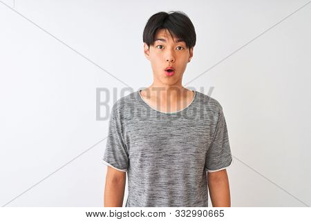 Young chinese man wearing casual t-shirt standing over isolated white background afraid and shocked with surprise expression, fear and excited face.