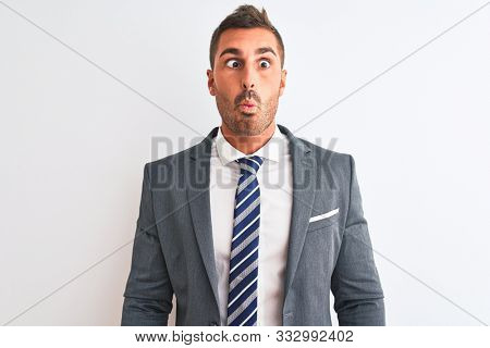Young handsome business man wearing suit and tie over isolated background making fish face with lips, crazy and comical gesture. Funny expression.