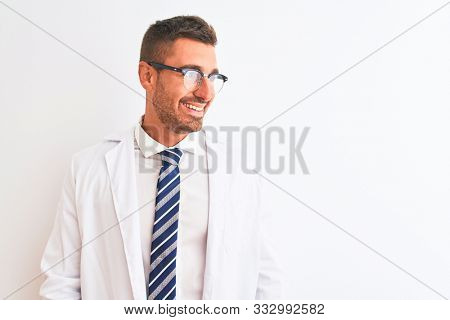 Young handsome therapist man over isolated background looking away to side with smile on face, natural expression. Laughing confident.