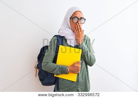 Young Arab student woman wearing hijab and backpack holding a book over isolated background cover mouth with hand shocked with shame for mistake, expression of fear, scared in silence, secret concept
