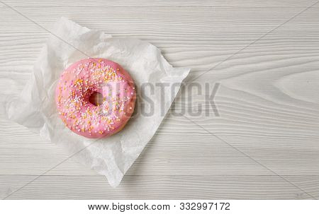 Freshly Baked Donut On Grey Wooden Desk, Top View