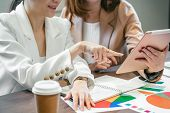 Closeup Two asian businesswomen working with the partner business by point finger to the technology tablet in modern meeting room, office or working space, coffee break, partner and colleague concept poster