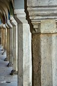 Arcades and stone columns in historic tenement houses on the market in Poznan poster