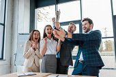 happy businessmen and multicultural businesswomen holding trophy in office poster