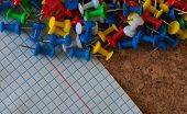 Group of colorful push pins on cork bulletin board poster