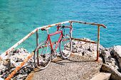 Red bicycle leaning on an iron fence in beach by sea. Bike leaning on railing on the pier facing adriatic sea horizon. Summer tourist season and travel. Bicycle on wonderful blue sea. poster