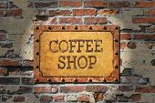 Coffee shop painted sign on heavily rusted metal plate, with rusted, riveted edges.That, on a very old brick wall. poster