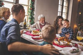 Beautiful Happy Family Gathered Around The Table, Having Christmas Dinner, Enjoying Their Time Toget