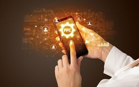 Female hand holding smartphone with PPC abbreviation, modern technology concept