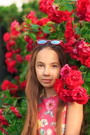 Portrait Of Cute Teen Girl Smiling At The Roses