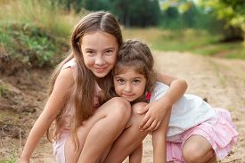 Portrait Of Two Cute Little Girls Embracing And Laughing At The Forest. Happy Kids Outdoors