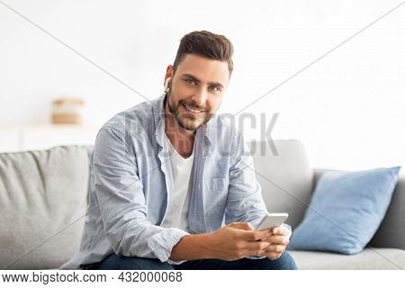 Handsome Millennial Man In Earbuds Using Smartphone And Smiling To Camera, Sitting On Sofa At Home,