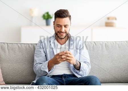 Young Man In Earbuds Chatting On Smartphone Sitting On Sofa At Home, Free Space. Technology And Gadg