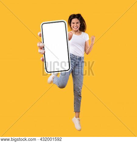 Woman Showing White Empty Smartphone Screen And Jumping Up