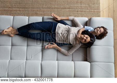 Happy Mixed Race Family Resting On Comfortable Sofa.