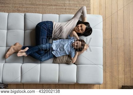 Relaxed Multiracial Diverse Family Daydreaming On Cozy Couch.