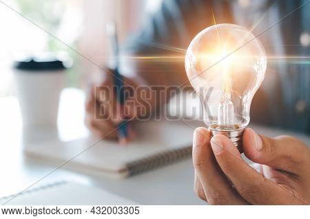 Innovation Through Ideas And Inspiration Ideas. Human Hand Holding Light Bulb To Illuminate, Idea Of