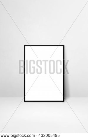 Black Picture Frame Leaning On A White Wall. Blank Mockup Template